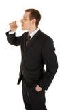 O homem novo em um terno de negócio preto prende um vidro o Foto de Stock