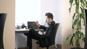 O homem novo em um terno está sentando-se no escritório, cansado, decola seus vidros e inclina-se para trás em seus fps da cadeir vídeos de arquivo
