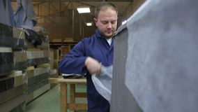 O homem novo em uma fábrica da mobília aplica uma espuma em uma parte do sofá filme