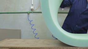 O homem novo em uma fábrica da mobília aplica uma espuma em uma parte do sofá video estoque