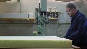 O homem novo em uma fábrica da mobília está cortando a espuma para o sofá filme