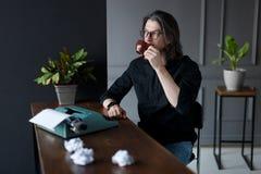 O homem novo em vidros pretos da camisa e do olho, bebe o café na mesa de trabalho para a ideia do trabalho, sobre interiores cin foto de stock