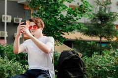 O homem novo em vidros vermelhos toma a imagem em seu telefone no parque Fotos de Stock