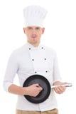 O homem novo engraçado na frigideira de jogo uniforme do cozinheiro chefe gosta de uma guitarra Fotografia de Stock Royalty Free