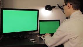 O homem novo entrega a datilografia no laptop verde da tela video estoque