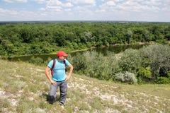 O homem novo escalou um monte sobre o rive Fotografia de Stock