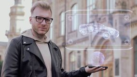 O homem novo esperto com vidros mostra a um holograma conceptual o carro de competência moderno vídeos de arquivo