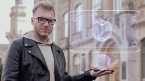 O homem novo esperto com vidros mostra uma maçã conceptual do holograma