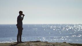 O homem novo está bebendo o café em uma praia video estoque