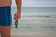 O homem novo está contra realizar do horizonte da água das ondas de areia da praia da costa de mar em seus óculos de sol da mão p imagem de stock royalty free