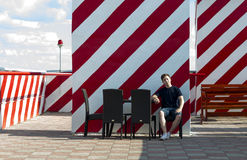 O homem novo está descansando o assento em uma tabela em um café Fotos de Stock Royalty Free