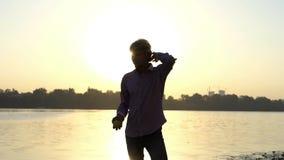 O homem novo está em um banco de rio no por do sol no slo-mo filme