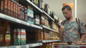 O homem novo está escolhendo o azeite em uma loja de mantimento, tomando garrafas da cremalheira vídeos de arquivo