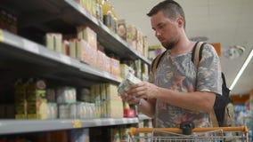 O homem novo está escolhendo bens no mantimento no supermercado, vista frontal video estoque