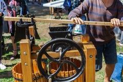 O homem novo está fazendo o suco de maçã usando a alavanca grande de uma imprensa da maçã foto de stock