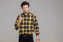 O homem novo está irritado no isolamento em Gray Background Imagens de Stock Royalty Free