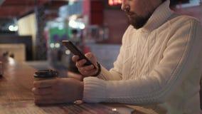 O homem novo está lançando através do feed noticioso em redes sociais em seu telefone filme