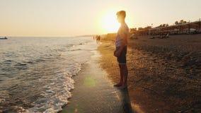 O homem novo está na praia, admira o por do sol filme