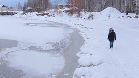 O homem novo está no banco coberto de neve do rio congelado no inverno filme