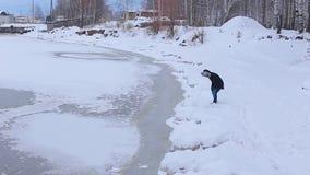 O homem novo está no banco coberto de neve do rio congelado senta-se então na neve vídeos de arquivo