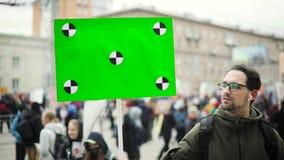 O homem novo está olhando o cartaz com a tela verde em sua mão na demonstração da cidade video estoque