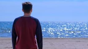 O homem novo está olhando o mar na praia da areia do mar, vista traseira video estoque