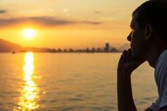 O homem novo está olhando o nascer do sol Fotografia de Stock