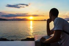 O homem novo está olhando o nascer do sol Imagem de Stock