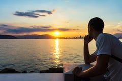 O homem novo está olhando o nascer do sol Fotos de Stock