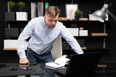 O homem novo está perto da tabela e dos olhares do computador no monitor imagem de stock