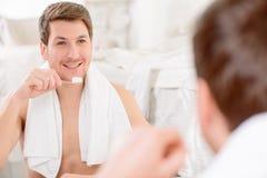 O homem novo está a ponto de escovar seus dentes imagens de stock