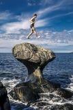 O homem novo está saltando na pedra, Kannesteinen, Noruega Fotografia de Stock Royalty Free