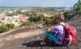 O homem novo está sentando-se em uma montanha e está olhando-se na cidade Fotografia de Stock Royalty Free