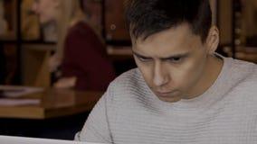 O homem novo está sentando-se na tabela com o portátil no café dentro video estoque