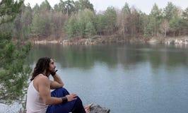 O homem novo está sentando-se no banco de rio relaxe Fotografia de Stock