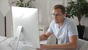O homem novo está sentando-se no computador na tabela e está conversando-se dentro video estoque