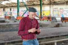 O homem novo está usando o smartphone Fotografia de Stock Royalty Free