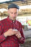 O homem novo está usando o smartphone Fotografia de Stock