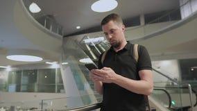 O homem novo está usando o smartphone que guarda o nas mãos no salão de construções modernas video estoque