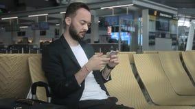 O homem novo está usando o telefone ao sentar-se na construção do aeroporto video estoque