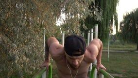 O homem novo executa um exercício do poder em barras desiguais filme