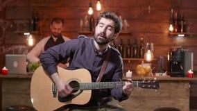 O homem novo executa uma música em uma guitarra acústica vídeos de arquivo