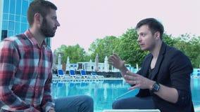 O homem novo explica nervosamente a seu amigo com suas mãos Gesticular bem sucedido, apaixonado do homem de negócios video estoque