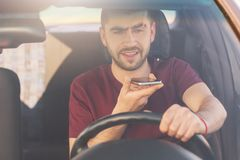 O homem novo farpado com restolho grosso faz a chamada de voz através do telefone celular, conduz o carro na alta velocidade, ris fotografia de stock