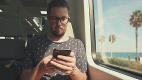 O homem novo farpado está sentando-se no vagão do trem suburbano, usando o smartphone filme