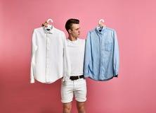 O homem novo faz uma escolha de uma camisa Azul ou branco? que escolhem? imagem de stock royalty free