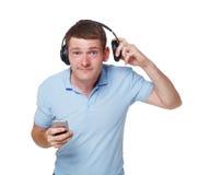 O homem novo feliz com fones de ouvido tenta ouvir alguém Imagens de Stock