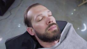 O homem novo feliz com uma barba encontra-se em uma cadeira e em um sorriso do ` s do barbeiro vídeos de arquivo