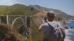 O homem novo feliz excitado do turista com trouxa toma a foto panorâmico do smartphone do Big Sur famoso da ponte da garganta de  filme