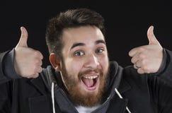 O homem novo feliz que mostra os polegares levanta sinais Fotografia de Stock Royalty Free